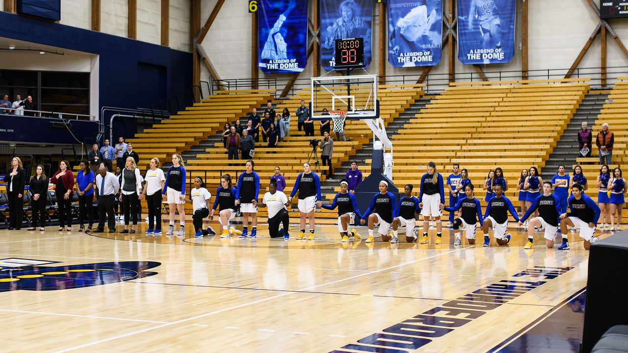 Many of the Gauchos Women's Basketball team take a knee during the national anthem.