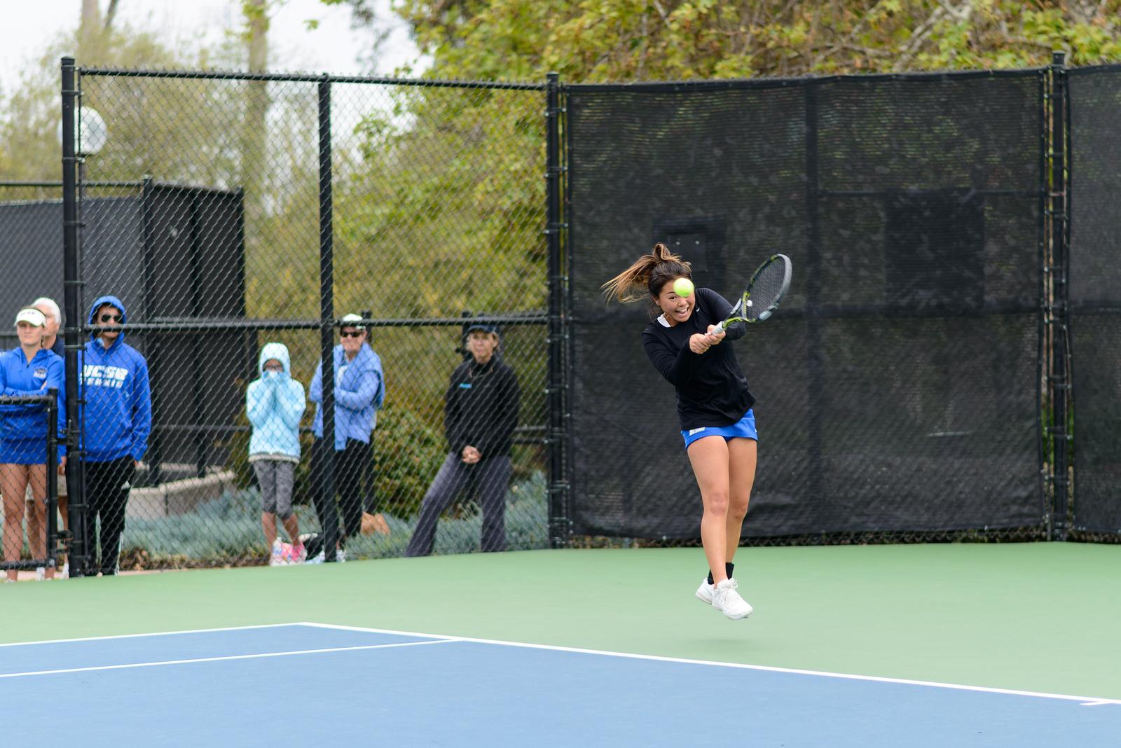 Stephanie Yamada jumps while swinging a solid backhand return.