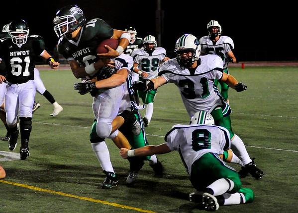 S0911FTBALL4.jpg Niwot High School QB Kelton Manzanares (16) is tackled by Standley Lake High School RB/DB Jay Polachek (8), FB/LB Conner Burgwald (31) and OL/DL Patrick Schall (53) at the Niwot vs. Standley Lake Football game at Longmont High School on Thursday night, Sept. 10, 2009.