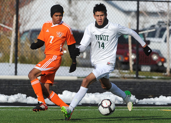 Niwot High School's Carlos Dominguez moves the ball past Andres Luna during a game against Denver West High School on Thursday, Oct. 25, at Frederick High School.<br /> Jeremy Papasso/ Camera