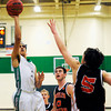 "Niwot High School's Forrest Lee takes a shot over Greeley Central's Zack Elrick, No. 5, and Shane O'Connell, No. 0, during a basketball game on Friday, Jan. 20, at Niwot High School. Niwot lost the game 49-45. For more photos of the game go to  <a href=""http://www.dailycamera.com"">http://www.dailycamera.com</a><br /> Jeremy Papasso/ Camera"