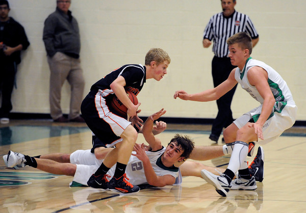 "Niwot High School's Jordan Keeler, middle, and Nate Merriman, right, fight for a loose ball with Greeley Central's Danny Butherus during a basketball game on Friday, Jan. 20, at Niwot High School. Niwot lost the game 49-45. For more photos of the game go to  <a href=""http://www.dailycamera.com"">http://www.dailycamera.com</a><br /> Jeremy Papasso/ Camera"