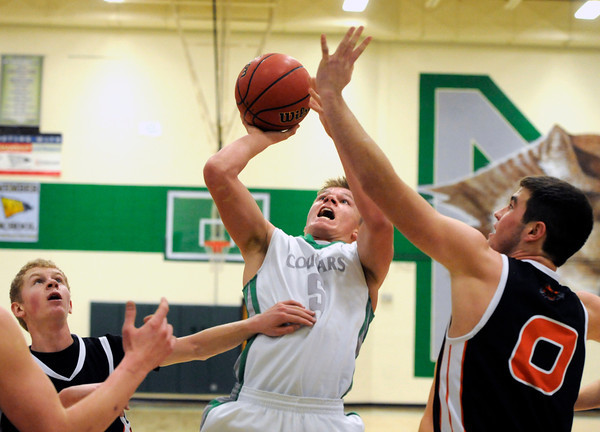 """Niwot High School's Nate Merriman takes a shot over Greeley Central's Shane O'Connell, right, during a basketball game on Friday, Jan. 20, at Niwot High School. Niwot lost the game 49-45. For more photos of the game go to  <a href=""""http://www.dailycamera.com"""">http://www.dailycamera.com</a><br /> Jeremy Papasso/ Camera"""
