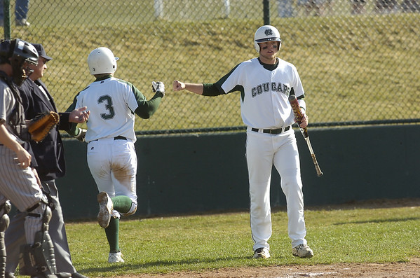 Brady Oleszczuk scores on a wild pitch and is congratulated by Veric Nichols during the Niwot High vs Mountain View game at Niwot High School on Wednesday April 7, 2010.<br /> Photo by Paul Aiken / The Camera