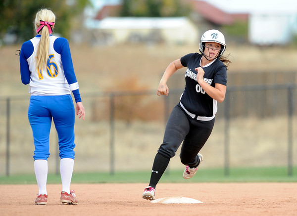 "Niwot High School's Katrina Hunt rounds third base past Katie Orona after an error during a game against Wheat Ridge High School on Saturday, Oct. 20, at the Aurora Sports Park in Aurora. Niwot won the game 1-0. For more photos of the game go to  <a href=""http://www.dailycamera.com"">http://www.dailycamera.com</a><br /> Jeremy Papasso/ Camera"