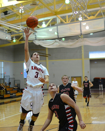 RYAN HUTTON/ Staff photo.<br /> North Andover's Kyle White (3) fires a shot up over the head of Reading's Mike Algeri (3) during the game at North Andover on Sunday. North Andover won 58-44.