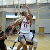 RYAN HUTTON/ Staff photo.<br /> North Andover's Brett Daley (11) fires a shot up as he collides with Reading's Andrew Bourque (30) during Sunday's game at North Andover. North Andover won 58-44.