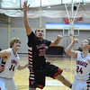 RYAN HUTTON/ Staff photo.<br /> Reading's Nathan McRetnolds (32) puts a shot up over North Andover defenders Jeff Warden (24) and Michael St. Cyr (34). North Andover won 58-44.