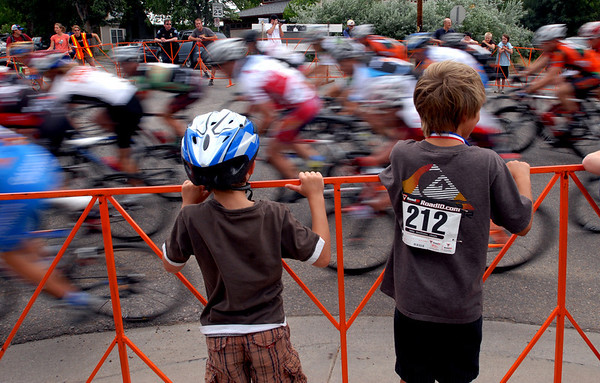 """Lukas Haug, left, and Andrew Vieregg, watch the pro riders fly by in the North Boulder  Park Classic on Saturday.<br /> For more photos of both pro men and women, go to  <a href=""""http://www.dailycamera.com"""">http://www.dailycamera.com</a><br />  Cliff Grassmick / July 10, 2010"""