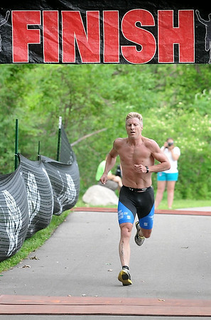 Dave Lyon crosses the finish line of the North Mankato Triathlon Saturday, winning the men's race. Photo by Pat Christman