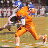 Matt Hamilton/The Daily Citizen<br /> NW44 takes the pitch on the option as NW QB takes a hit Friday.