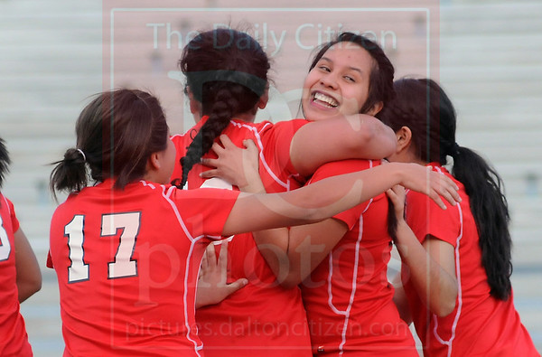 Matt Hamilton/The Daily Citizen<br /> D9 smiles as her teammates hug her after scoring Dalton's 3rd goal Tuesday.
