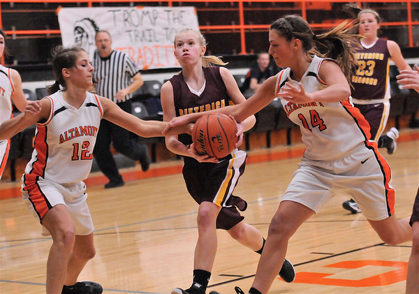 Dieterich's Courtney Flach tries to drive past Altamont's Madison Ohnesorge (12) and Lauren Ohnesorge.