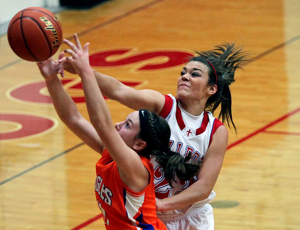 St. Anthony's Makayla Walsh, right, swats the ball away from Newton's Megan Jansen in the first half of the game at St. Anthony High School. The Bulldogs evened their record at 1-1 with a 41-30 victory.