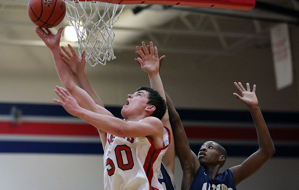 Effingham senior Clark Williamson (50) attempts to make a basket as Althoff Catholic High School's Brendon Gooch attempts to block him. Effingham lost 41-39.