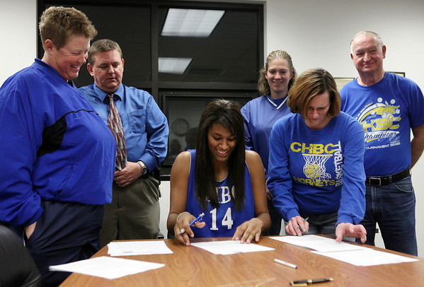 From left: Cowden-Herrick/Beecher City head girls basketbal coach Caroline Wendte, Cowden-Herrick high school principal Jerry Phillips, Athletic Director Jackie Mette, and assistant coach Larry Young watch as Micah Jones and her mother, Laura Endsley, sign paperwork accepting Southern Illinois University Edwardsville's basketball scholarship offer at Cowden-Herrick High School.