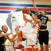 Effingham's Kevin Daugherty drives to the basket around, Althoff Catholic's Eric Merten and Kevin, Renner at the Enlow Center during the St. Anthony Turkey Tournament.