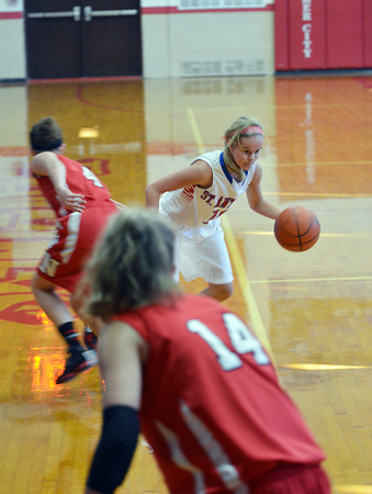 St. Anthony's Morgan Gardewine dribbles past Neoga's Madison Butler (4) while EC Thies stands in the foreground defensively (14) during the NTC tournament championship in Beecher City.