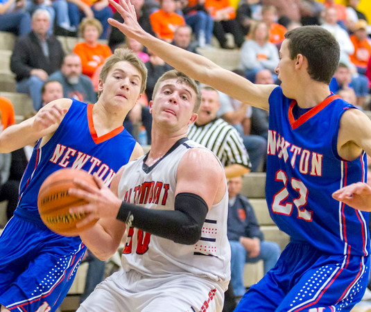 Altamont's Klaiton Wolff drives to the basket while Newton's Collin Harris (right) and Michael Koebele (left) close in at the Cumberland Thanksgiving Tournament.