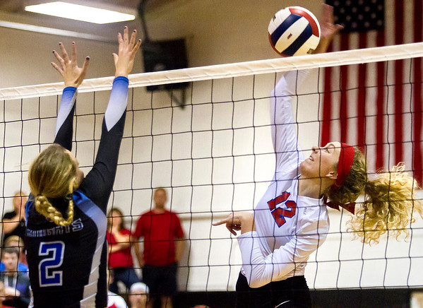 St. Anthony's Marci Mills, right, connects on a hit as Blue Ridge's Olivia Reynolds attempts the block during a sectional semifinal in Fisher.