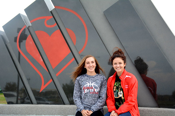 Effingham cross country runners Miranda Fox and Alexis Monnet sit in front of Effingham High School. The two competed at sectionals Saturday, and crossed the finish line together after Monnet had a seizure during the race.