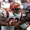 BALTIMORE, MD - SEPTEMBER 24: Half back Corey Dillon #28 of the Cincinnati Bengals carries the ball around the right side of the line of scrimmage to make some yardage only to find Defensive End Rob Burnett #90 of the Baltimore Ravens there trying to tackle him in a NFL game at PSINet Stadium on September 24, 2000 in Baltimore, Maryland. The Ravens won the game 37-0. (Photo by Michael J. Minardi) *** Local Caption *** Corey Dillon;Rob Burnett