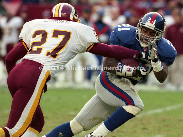 WASHINGTON, DC - DECEMBER 3: Running Back Tiki Barber #21 of the New York Giants runs for some good yardage pursued by Safety Mark Carrier #27 of the Washington Redskinsin a NFL game at FedEx Field on December 3, 2000 in Landover, Maryland. The Giants won 9 to 7. (Photo by Michael J. Minardi) *** Local Caption *** Tiki Barber;Mark Carrier