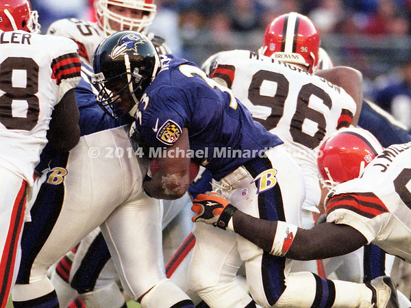 BALTIMORE, MD - NOVEMBER 26: Running Back Priest Holmes #33 of the Baltimore Ravens gains a few yards before being tackled by Jamir Miller #95 of the Cleveland Browns in a NFL game at PSINet Ravens Stadium on November 26, 2000 in Baltimore, Maryland. The Ravens won 44 to 7. (Photo by Michael J. Minardi) *** Local Caption *** Priest Holmes;Jamir Miller