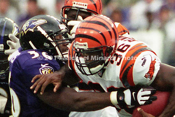 BALTIMORE, MD - SEPTEMBER 24: Half Back Brandon Bennett of the Cininnati Bengals carries the ball for extra yardage while Linebacker Anthony Davis #56 of the Baltimore Ravens and teammate Defensive End Michael McCrary #99 tackle Bennett during a NFL game at PSINet Stadium on September 24, 2000 in Baltimore, Maryland. The Ravens won 37-0. (Photo by Michael J. Minardi) *** Local Caption *** Brandon Bennett;Anthony Davis;Michael McCrary