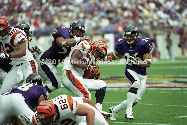 BALTIMORE, MD - SEPTEMBER 24: Halfback Corey Dillon #28 of the Cincinnati Bengals carries the football for several good yards until he is tackled by Linebacker Jamie Sharper #55 of the Baltimore Ravens and his teammate Corner back Rod Woodson #26 during a NFL game at PSINet Stadium on September 24, 2000 in Baltimore, Maryland. The Ravens defeated the Bengals 37-0. (Photo by Michael J. Minardi) *** Local Caption *** Corey Dillon;Jamie Sharper;Rod Woodson