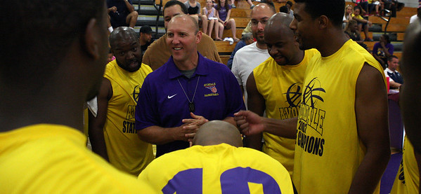 Former Avondale head coach Tim Morton (center), has a sideline chat with his 2002 state championship team during a game pitting the state championship squad against a team of Avondale all-stars past and present Friday, June 27, 2014. (Special to The Oakland Press/LARRY McKEE)
