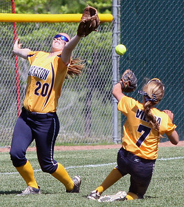 Katelyn Kuenzel (20) and Rachel Vieira, Clarkston, attempt to catch a fly ball and avoid a collision during district softball action against Lake Orion at Lake Orion High School Saturday, May 31, 2014. (Special to The Oakland Press / LARRY McKEE)