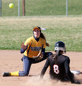 Rachel Vieira, Clarkston, makes a play at second base as Sydney Heath (8), Troy, slides into the base during varsity softball action at Clarkston Wednesday, April 23, 2014. (Special to The Oakland Press / LARRY McKEE)