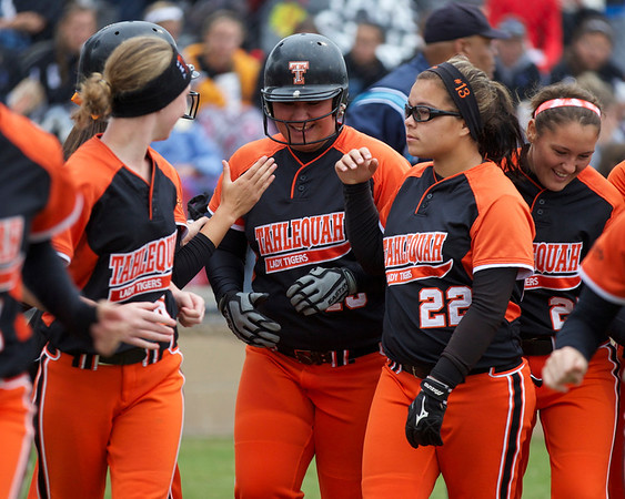 Special photo by Von Castor<br /> Tahlequah's Bub Peters, center, is congratulated by members of the Lady Tigers after hitting a home run in the Lady Tigers' Class 5A semifinal game against Carl Albert.