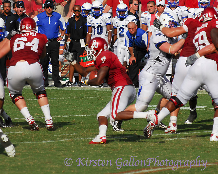 Murray cuts through the hole created by his offensive line.  #64 Gabe Ikard puts a block on a Falcon defensive lineman.
