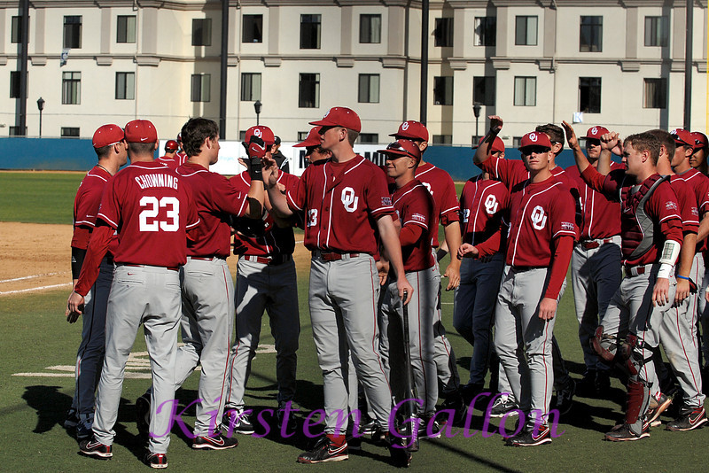 The Sooner team greets the incoming runners as Oklahoma's bats get off to a good start.