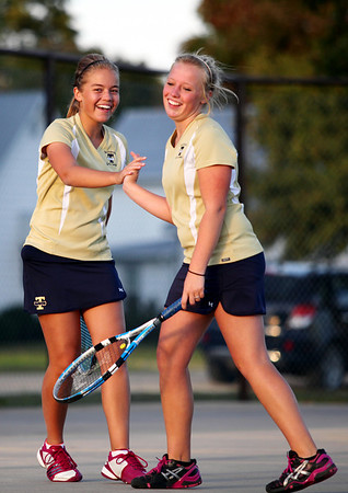 Allison Vogt, left, and Cheyenne Lueken of Teutopolis share a handslap after wrapping up a 10-0 doubles victory over their Vandalia opponents Oct. 9. The Wooden Shoes completed a 12-0 regular season with an 8-1 victory.