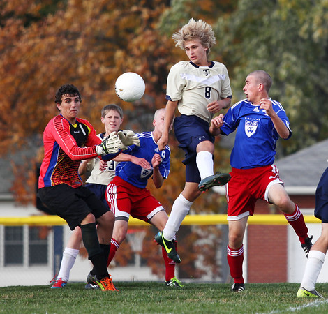 Andrew Kowalski (8) of Teutopolis tries to clear the ball away from goalkeeper Seth Belford (left), as Carlinville's Kyle Levan (9) and Jake Pohlman (right) during the Class 1A sectional semifinal at St. Anthony.
