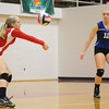 St. Anthony's Rachel Schultz (red) digs out a ball while teammate Megan Nuxoll (12, blue) looks on at Goff Gym.