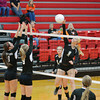 Altamont's Gabby Alwardt (1) spikes a ball while Beecher City's Kisten Buzzard (left) and Leah Kelly (9, center) go for a block.