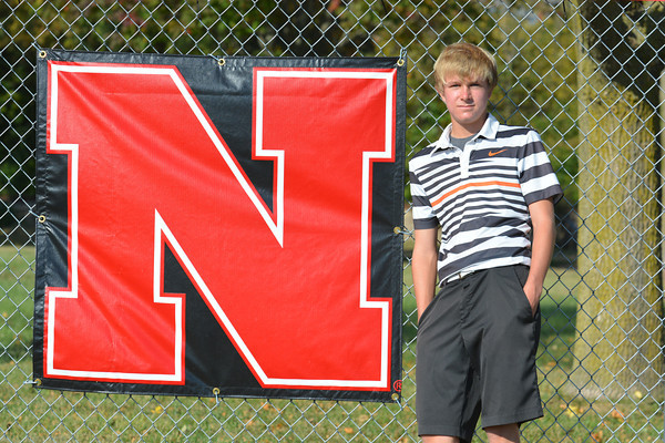 Neoga sophomore Luke Baker, the entirety of the Neoga golf team, poses in front of a Neoga High School banner.