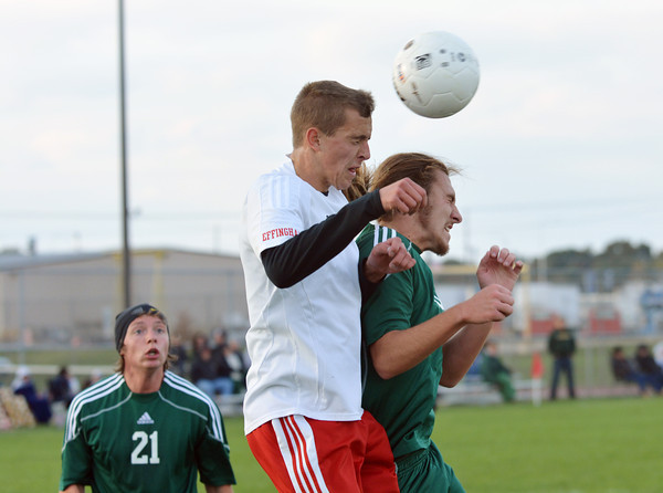 Effingham's Jason Pike (center) and Mattoon's Chase Harvey (right) go up for a header while Mattoon's Matt Calio (21) looks on Wednesday at the Class 2A Effingham Regional.