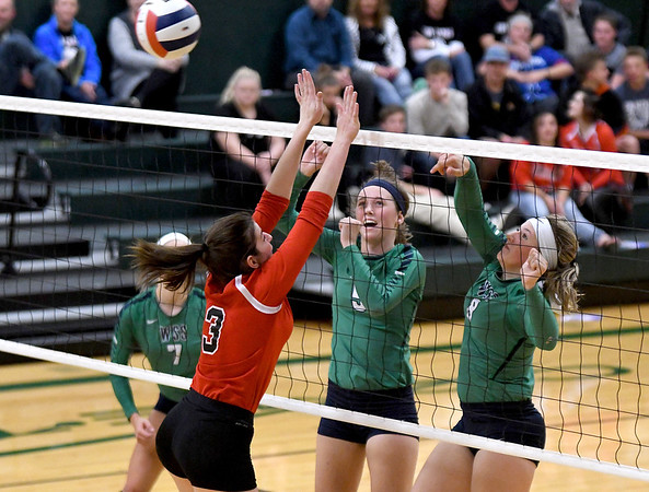 Windsor/Stew-Stras' Mackenzi Tabbert (8, right) hits a ball over the defense of Chrisman's Kodey Bush (3) as W/SS' Kasy Bean (5, middle) provides support at the net during the Class 1A Stew-Stras Regional championship game.