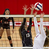 St. Anthony's Jenna Woltman (right) sets the ball while North Clay's Darcy Fender (13) attempts a block.