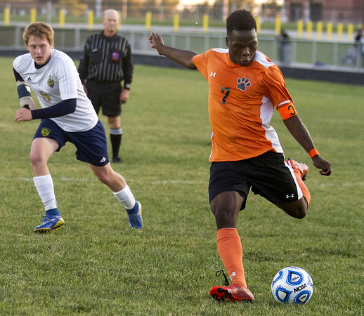 Beardstown's Murphy Domitien (7) goes to strike the ball inside the box as Teutopolis' Caleb Ordner, left, tries to catch up.