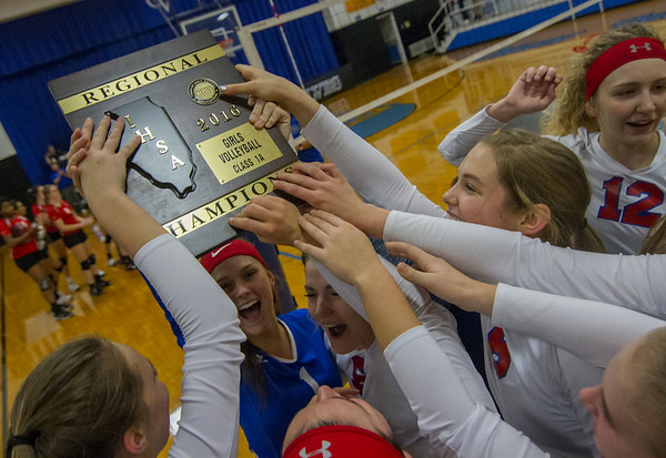 Members of the St. Anthony volleyball team grab on to their regional title after defeating Neoga 25-17, 25-6 in the Class 1A Okaw Valley Regional championship in Bethany.