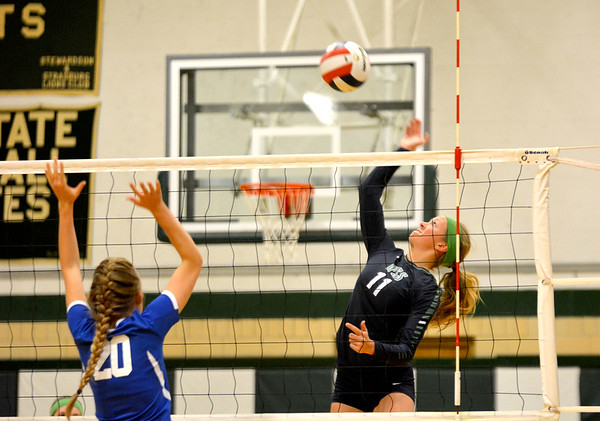 Windsor/Stew-Stras' Megan Schlechte rises up for a kill attempt past the defense of Martinsville's Alex Stone (20) at Stew-Stras.