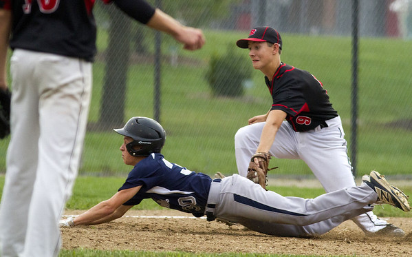 South Central's Logan Lotz slides into third base while North Clay's Harman Clifton makes the tag out as pitcher Brandon Repking watches from the mound.
