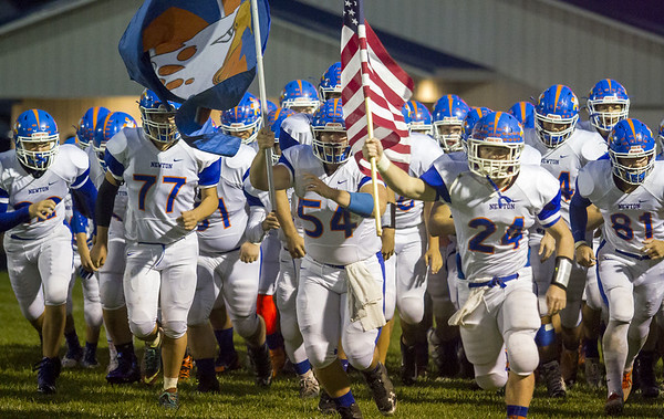 Newton's Mitch Bierman (24) and Gabe Fulton (54) lead their team out onto the field at Flora.