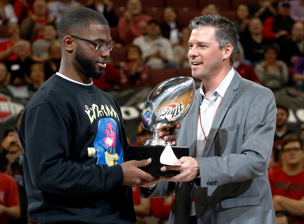 . Teddy Greenstein, right, a sportswriter for the Chicago Tribune, presents Ohio State quarterback J.T. Barrett with the Chicago Tribune Silver Football Award during the first half of an NCAA college basketball game between Northwestern and Ohio State, Sunday, Jan. 22, 2017, in Columbus, Ohio. (AP Photo/Jay LaPrete)